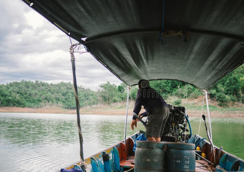 Boat driver was on the back of long tail boat in speed floating on green water of dam called Kaeng Krachani. Thailand royalty free stock images
