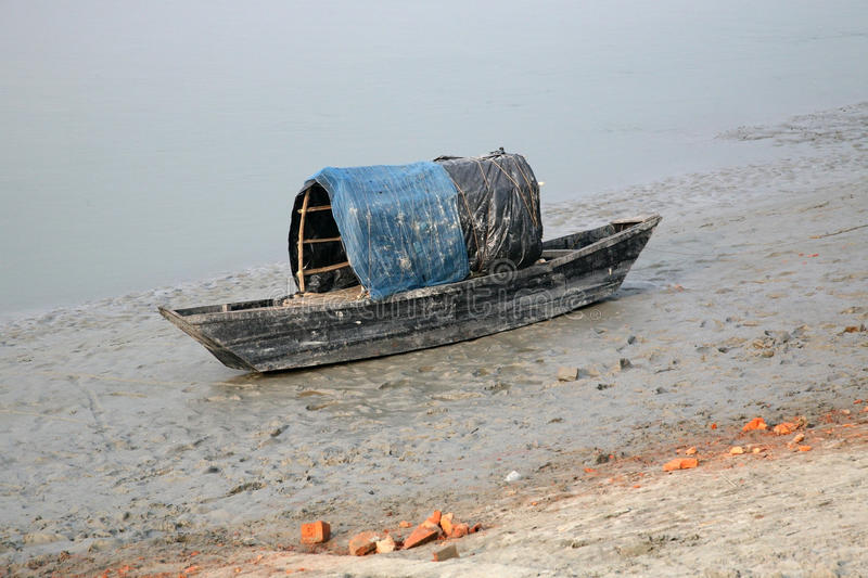 Boat of fishermen stranded in the mud at low tide on the river Malta near Canning Town, India. Boat of fishermen stranded in the mud at low tide on the river royalty free stock image
