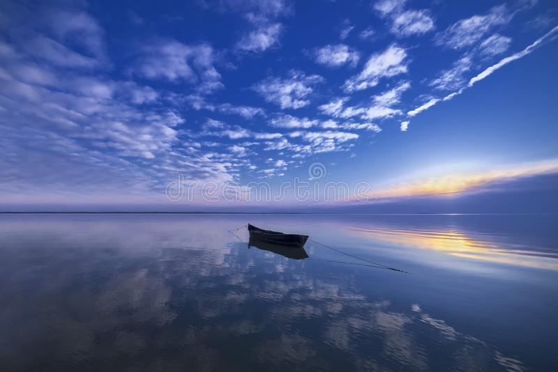 Boat floating on calm lake. An boat floating on the calm waters of lake Razelm, Romania royalty free stock image