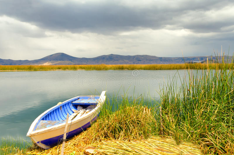 Boat and Floating Island. Boat on the shore of a manmade floating island on Lake Titicaca in Peru royalty free stock photography