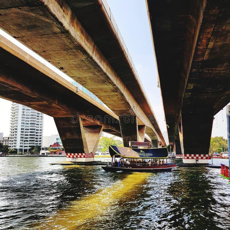 Boat floating on river under bridge. Bangkok, thailand, traveling, tourism, architecture, landmark, outdoor, leisure, vehi, vehicle, high, tall, shadow royalty free stock image