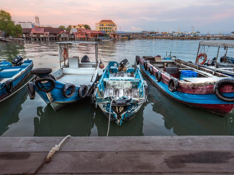 Boat floating beside wooden walk path to Tan Jetty, George Town, Penang, Malaysia royalty free stock photography