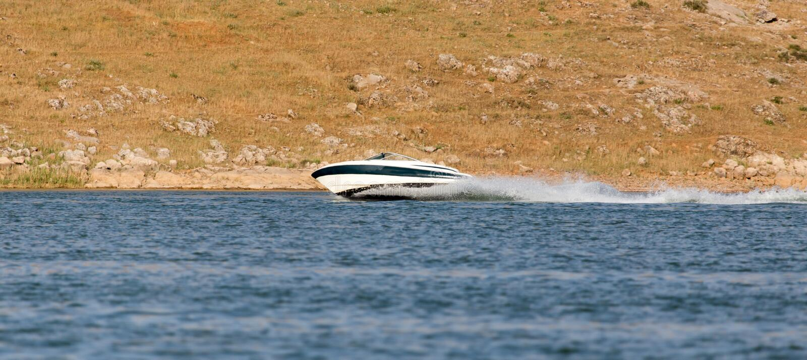 Boat floats on the lake speed. In the park in nature royalty free stock image