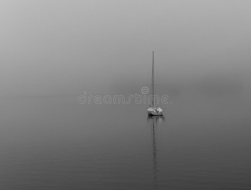 Boat on foggy lake stock photo