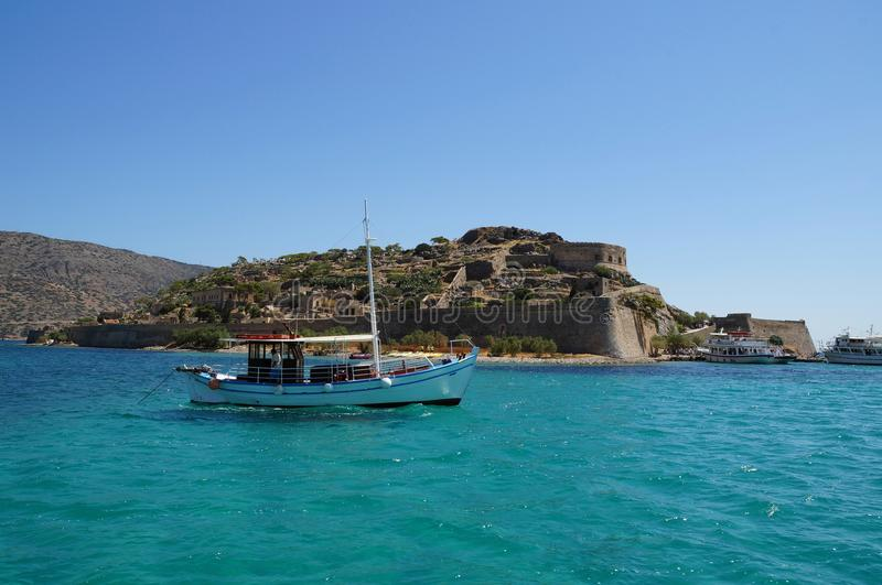 A boat in front of Spinalonga island royalty free stock image