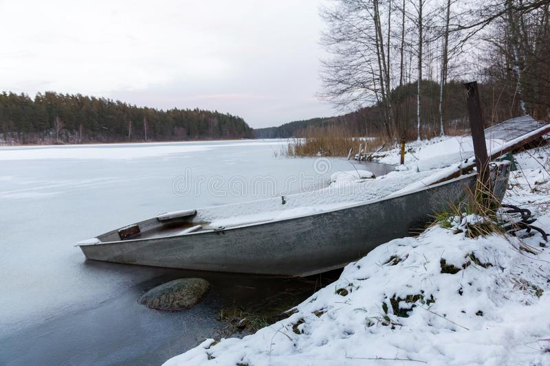 Boat frozen in the ice on the lake coast with trees and forest i. N the background in winter stock photo
