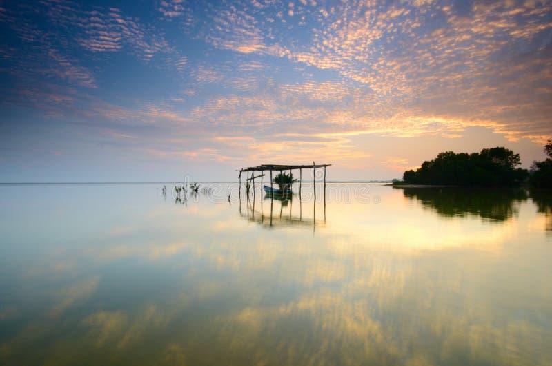 Boat on the garage at beautiful sunrise time.  Jubakar beach kelantan,  malaysia. Soft focus due to long exposure. stock photo