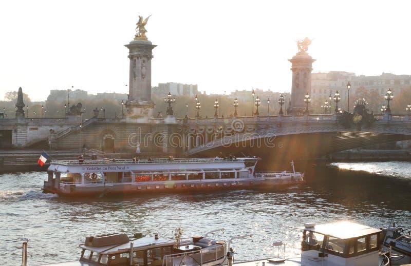 Boat going under a bridge. Paris, France stock photos