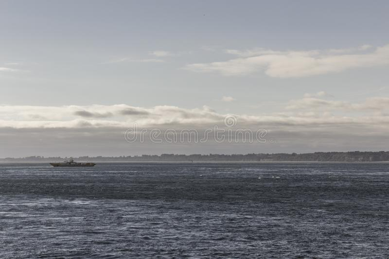 Boat on the horizon. Line in the middle of the sea. Clouds and mountains in the background royalty free stock image