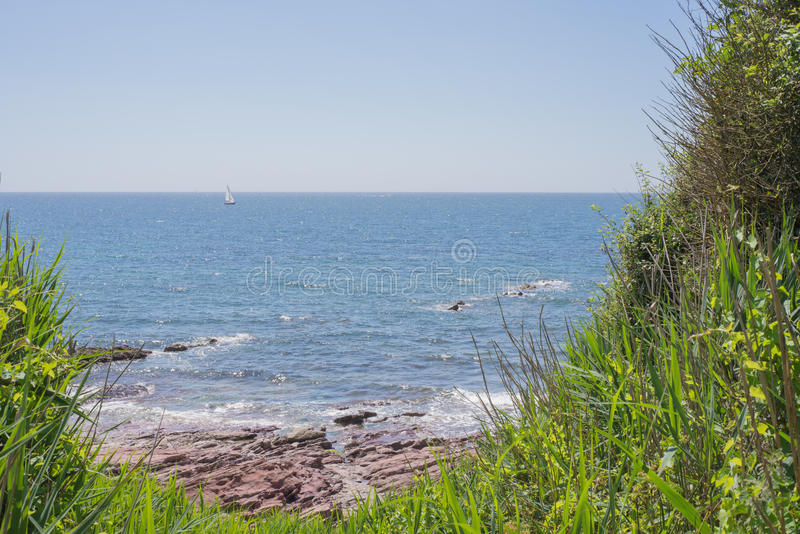 Boat on the horizon. Looking out at a yacht sailing on a Summers day. Taken from Wembury Beach, Devon royalty free stock images