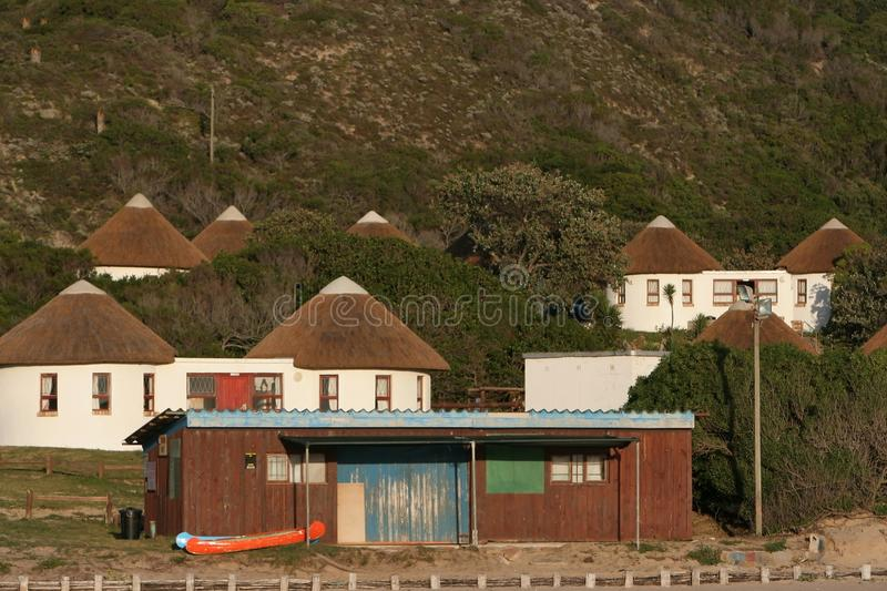 Boat House and Holiday Houses. A old wooden boat house with white thatch holiday houses in the background stock image