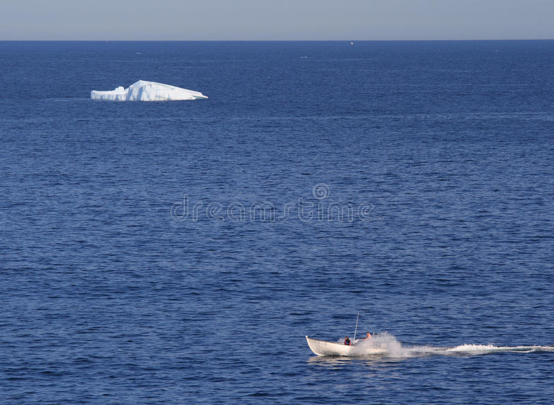 Boat and Iceberg at St. Anthony. ST. ANTHONY, CANADA – JULY 23: A boat passes an iceberg on July 23, 2011 in St.Anthony, Newfoundland. Icebergs from stock photo