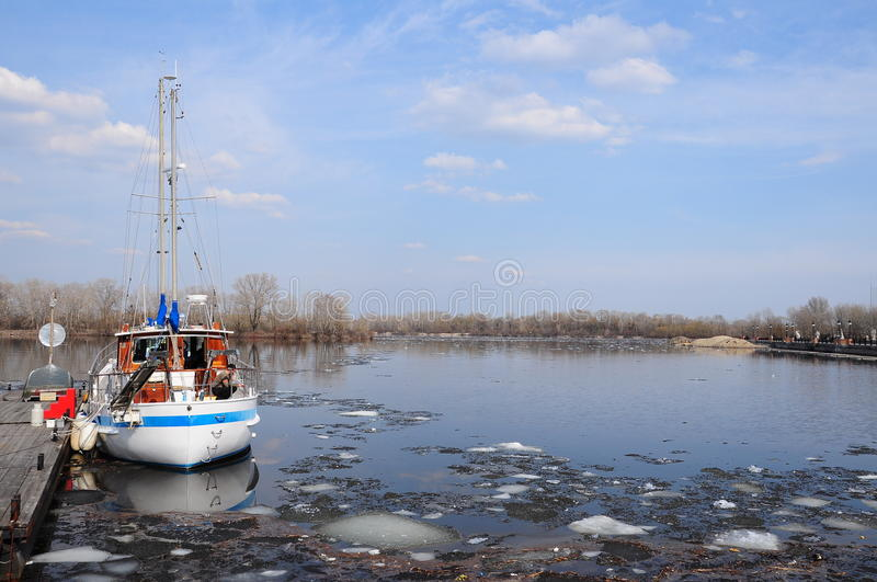 Boat on icy river (lake) stock image