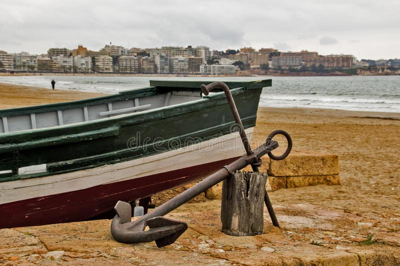 Boat with its anchor near to the sea stock photography