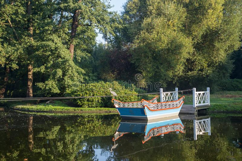 Boat and jetty in Frederiksberg Gardens, Denmark. Frederiksberg, Denmark - September 8, 2016: A wooden boat and a jetty in Frederiksberg Gardens stock photos