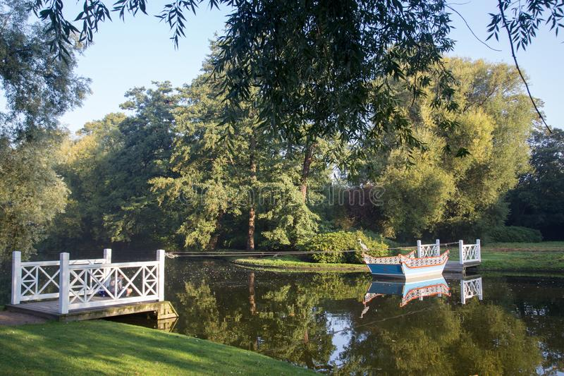 Boat and jetty in Frederiksberg Gardens, Denmark. Frederiksberg, Denmark - September 8, 2016: A wooden boat and two jetties in Frederiksberg Gardens royalty free stock photography