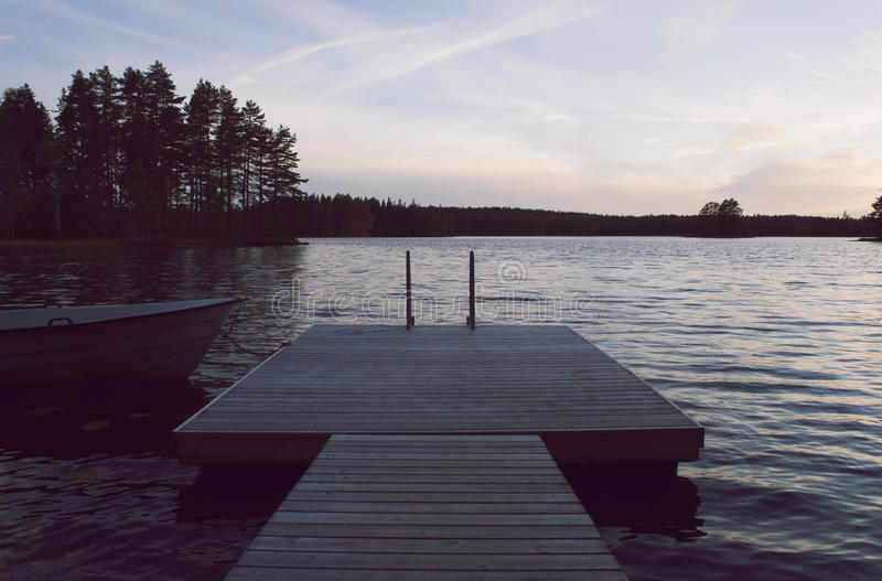 Boat and jetty by lake in beautiful sunset. Boat tied to an empty jetty. Sunset over a lake a beautiful, colorful, summer evening. Värmland, Sweden royalty free stock photos