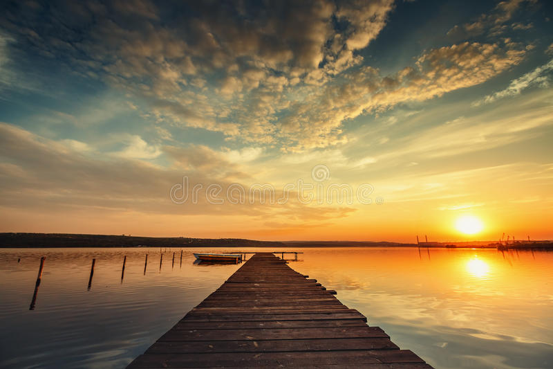 Boat and jetty on lake with a reflection in the water at sunset royalty free stock photo