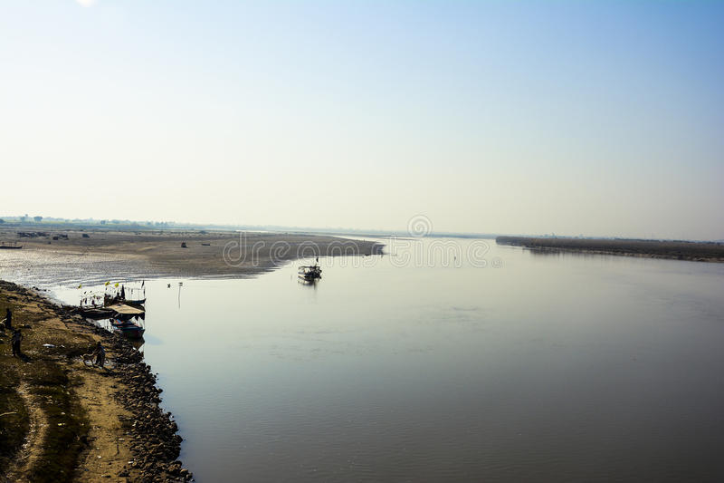 Boat in Jhelum River. Khushab Bridge, Punjab, Pakistan. Old rail track bridge can also be seen in the image. Jehlam River or Jhelum River is a river that stock photo