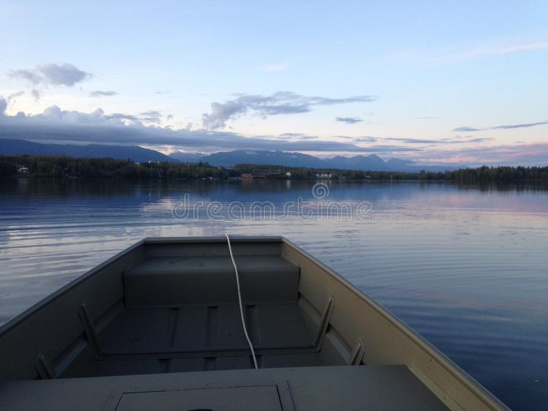 Boat on lake in Alaska. Jon boat on calm lake in Alaska stock images