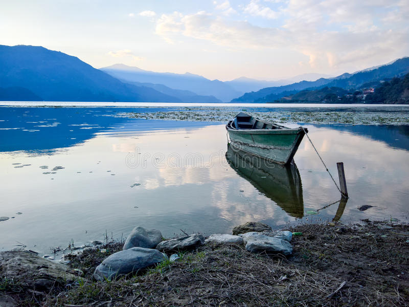 Boat on Lake at Sunset. A boat floating on a lake in nepal at sunset stock photography