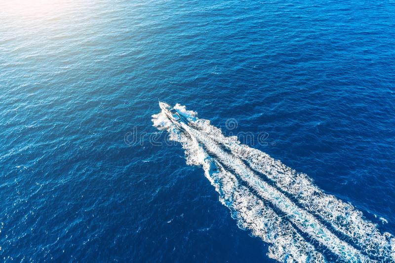 Boat launch at high speed floats to sunlight in the Mediterranean, aerial top view.  royalty free stock photo