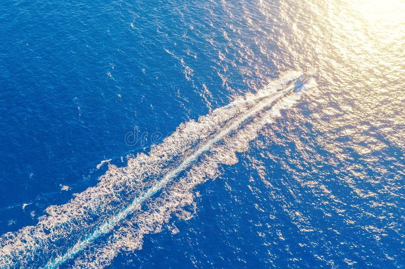 Boat launch at high speed floats to sunlight in the Mediterranean, aerial top view.  royalty free stock photography