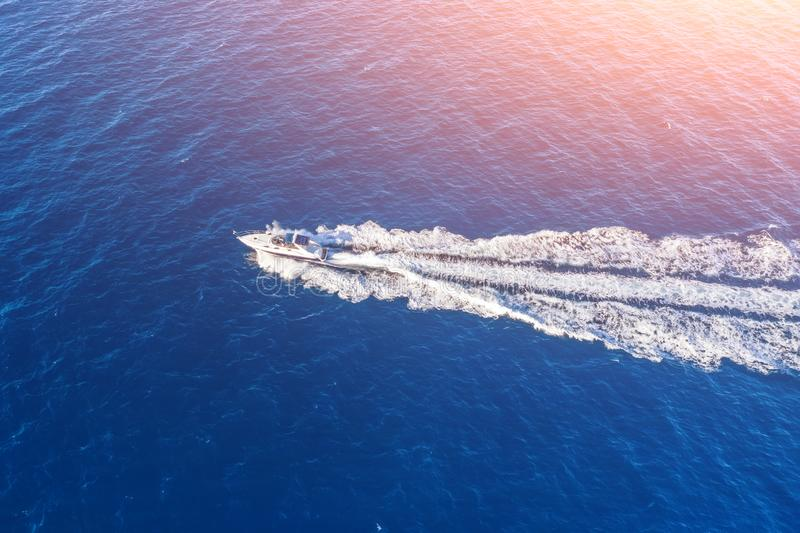 Boat launch at high speed floats to sunlight in the ocrean, aerial top view.  stock photography