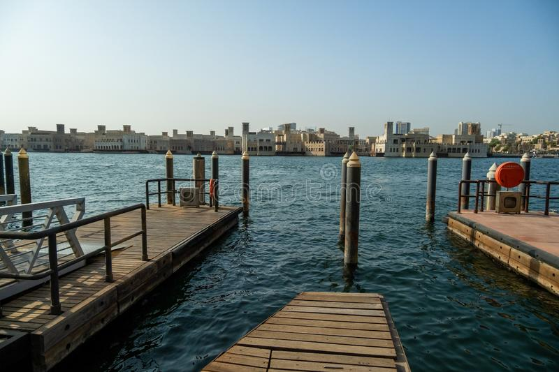 Boat marina on the canal in the middle of the city. View of Dubai Creek from the Deira area. Wooden platforms near blue water stock photography