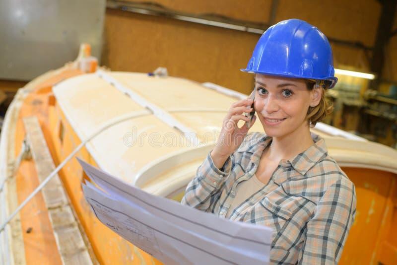 Boat mechanic smiling while using phone at garage royalty free stock photo