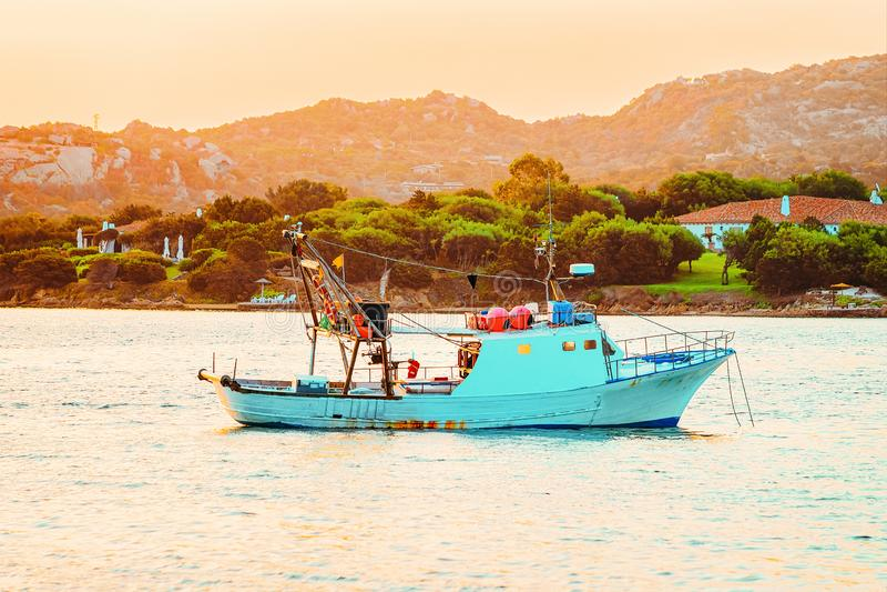 Boat on the Mediterranean Sea in Costa Smeralda. In Sardinia in Italy at sunrise stock photos
