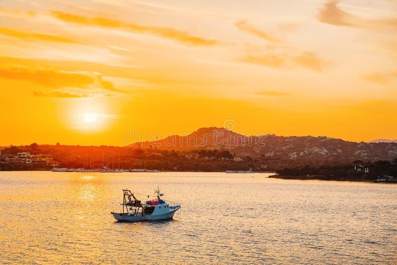 Boat in the Mediterranean Sea on Costa Smeralda. In Sardinia in Italy at sunrise royalty free stock photo