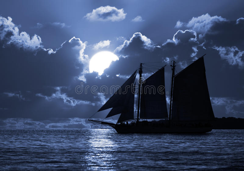 A boat on the moonlit seas stock photo