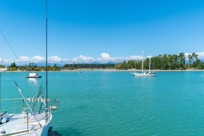 Waimea Estuary at Mapua on Tasman Bay. Boat moored in bay, Waimea Estuary at Mapua on Tasman Bay with yacht moored center stock image