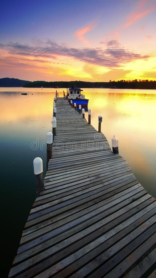 Boat moored by jetty at sunset royalty free stock photography