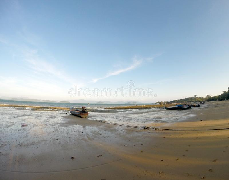 The boat moored on a sandy beach at low tide until dry.view from wide len. The boat moored on a sandy beach at low tide until dry royalty free stock photo