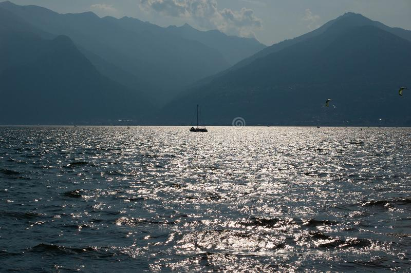Boat in the mountain lake. District of Como Lake, Colico, Italy, Europe. Evening light. White boat in the mountain lake. District of Como Lake, Colico, Italy stock photo