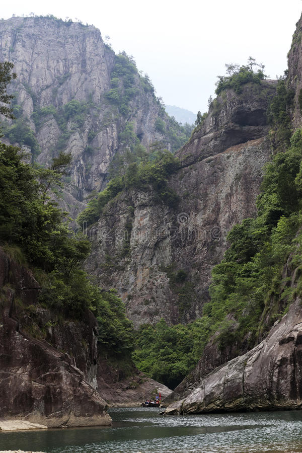 The boat moving in canyon streams. Calm streams, steep mountainside, driving the boat stock image