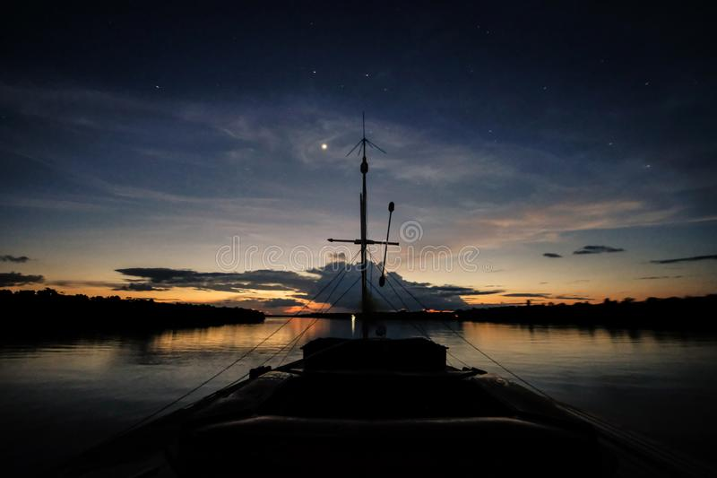 A boat navigates the Javari River after the sunset stock images