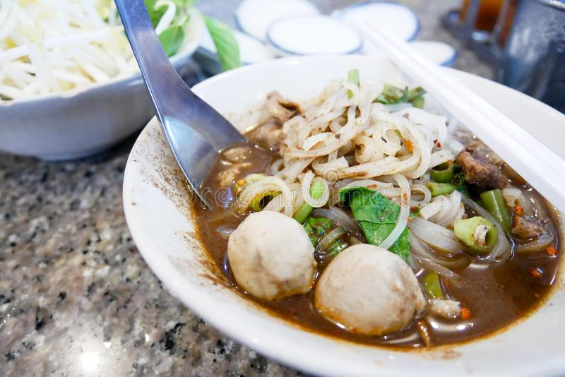 Boat noodle Thai food in the table. Boat noodle Thai food with meat ball and vegetable in the table stock photography