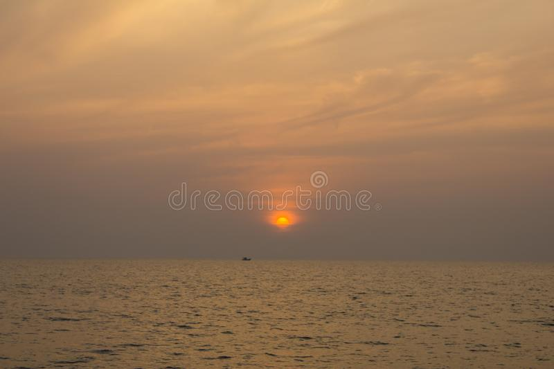 Boat in the ocean on a background of purple sunset sky with bright yellow sun. A boat in the ocean on a background of purple sunset sky with bright yellow sun stock photos