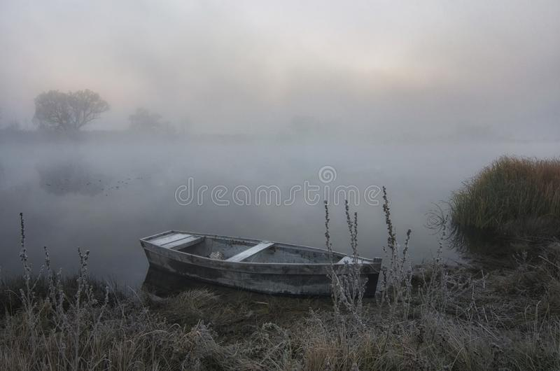 Boat off the coast on a foggy spring morning stock photo