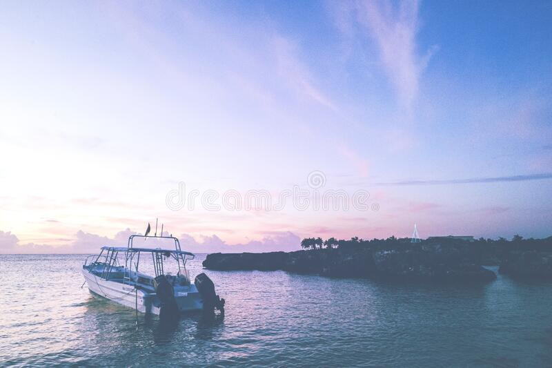 Boat off coastline at sunset stock images