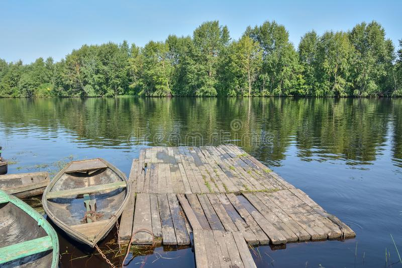 Boat at the old wooden pier on the river royalty free stock photo