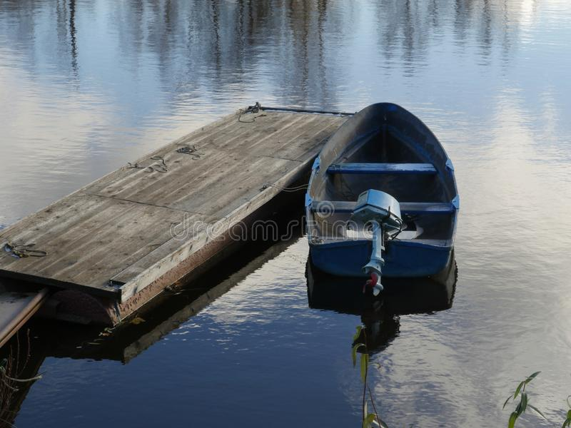 Boat with an outboard motor. Moored stock photography