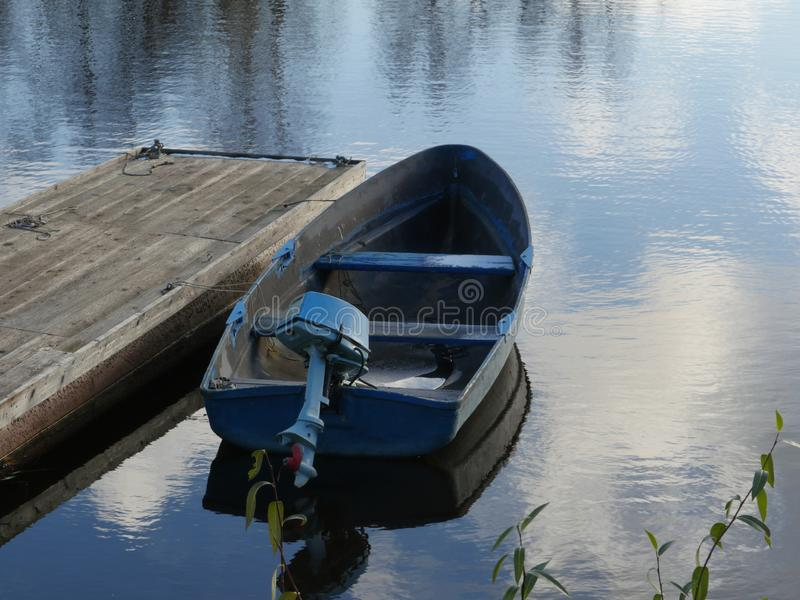 Boat with an outboard motor. Old boat with an outboard motor moored at the pontoon royalty free stock photography
