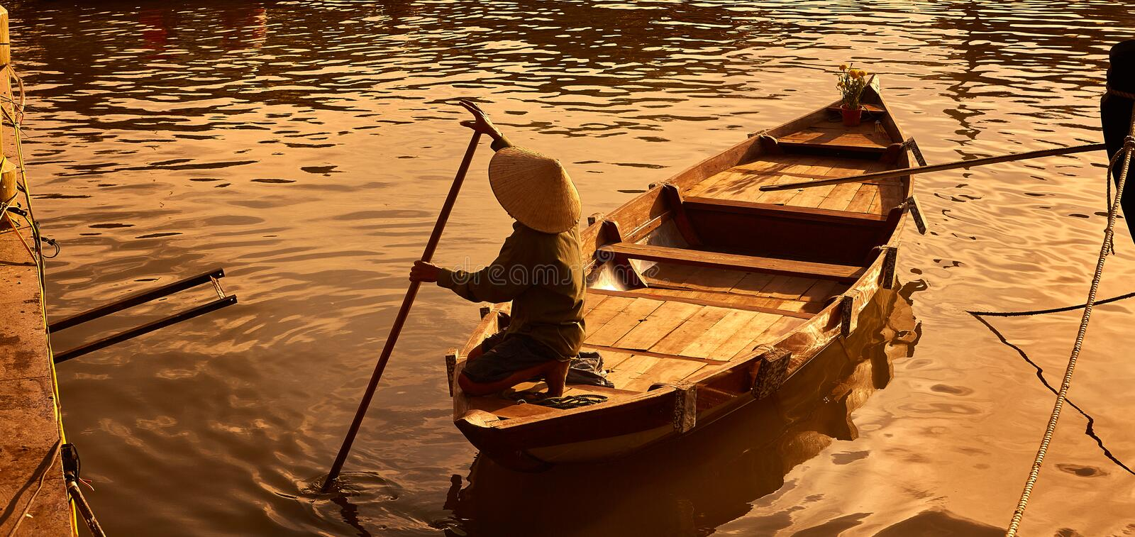 Boat paddler golden hour. A boat paddler in golden hour work hard to attract their customers for memorable and relaxing moment boat ride in Hoi An ancient town royalty free stock image