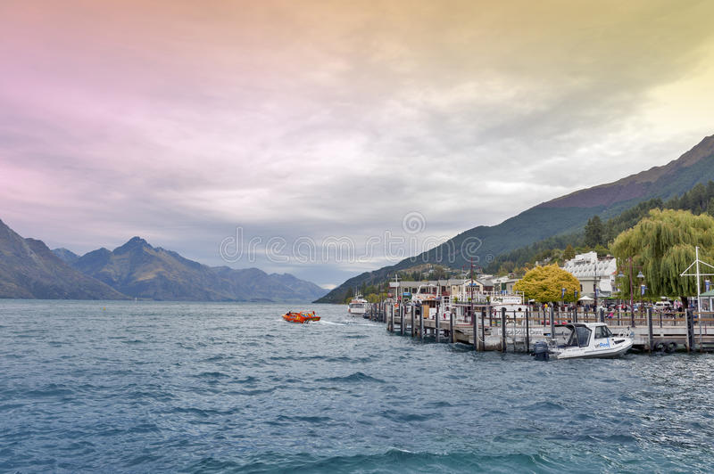 Boat piers at Queenstown lakefront by Lake Wakatipu, New Zealand, with speed jet boat seen in distant. Queenstown, New Zealand - March 2016: Boat piers at stock image
