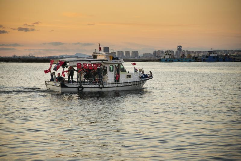 Boat with poeple and they have Turkish flags on it. Izmir, Turkey - October 29, 2017: boat with poeple and they have Turkish flags on it on the aegean sea and royalty free stock photos