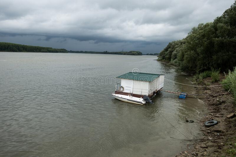 Boat and pontoon alongside Danube river,  in Braila,  Romania,  stormy spring day. Outdoors royalty free stock image